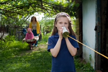 A girl with a toy-telephone and her mother and sister Stock Photo - 7078163