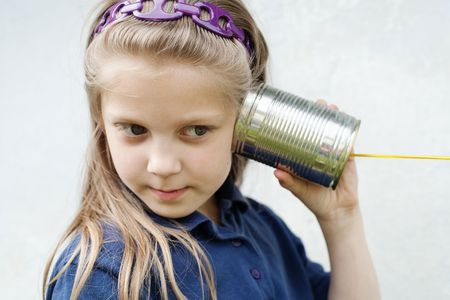 An image of a little girl with a toy-telephone  photo