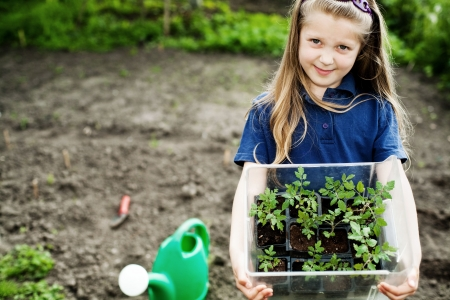 watering pot: An image of a nice little girl with seedlings