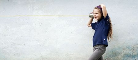 tin can telephone: A girl playing with a toy-telephone outdoors