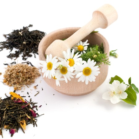 An image of wooden mortar with flowers in it and tea photo