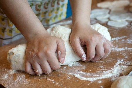 haciendo pan: Una imagen de manos haciendo masa sobre la mesa