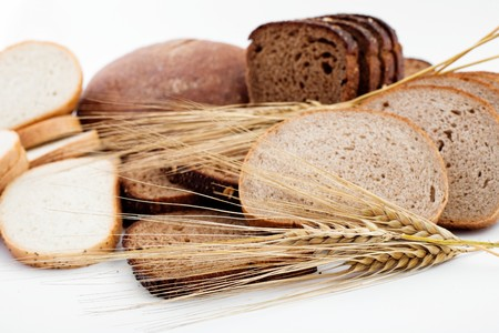 Various sorts of bread and spikes on white background photo