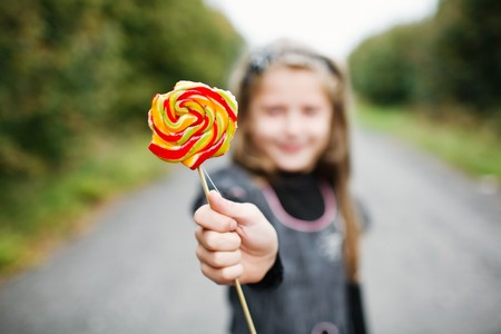 An image of little girl wit lollipop in his hand photo