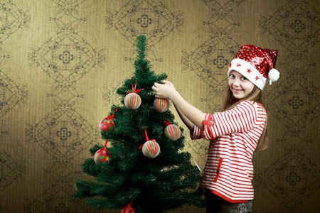 decorating christmas tree: A little girl decorating a new year tree with balls