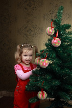 A nice girl decorating a new year tree with balls photo