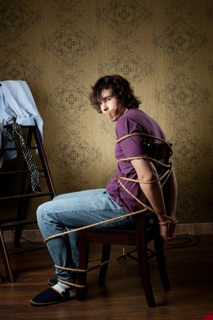 convict: An image of a young man tied on a chair