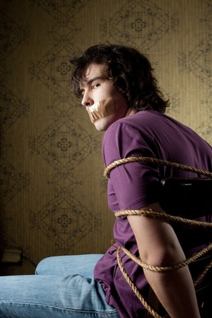 hostage: An image of a young tied man on a chair Stock Photo