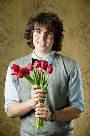A young student in glasses with red tulips Stock Photo - 8271465