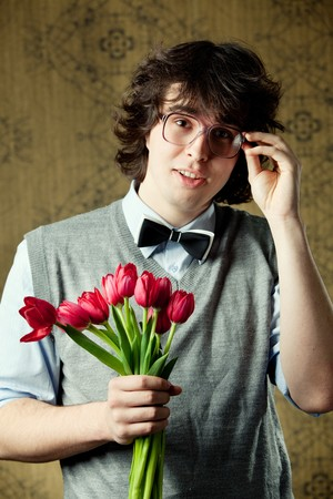 A young student in glasses with red tulips Stock Photo - 8271441