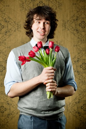 A young cheerful man with red tulips Stock Photo - 8271466