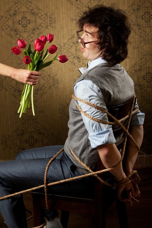 An image of a bound man on a chair and red tulips photo