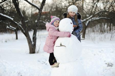 Little girls portrait, happy posing with snowman