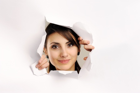 Young woman looking through hole in paper Stock Photo - 8761568