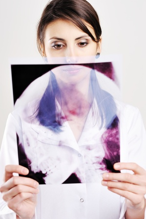 An image of female doctor examing x-ray of scull Stock Photo - 8761622