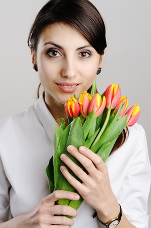 A young woman holding a bunch of tulips photo