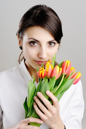 An image of young woman holding a bunch of orange tulips photo