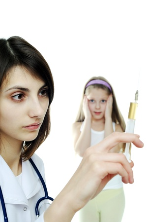 Doctor getting ready to make an injection to a child photo