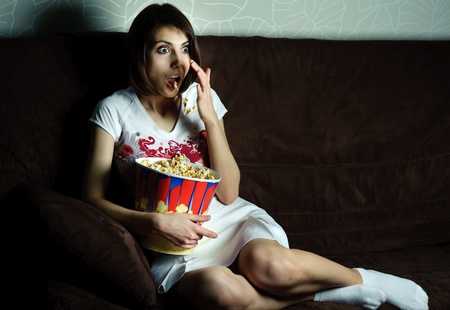 An image of woman watching TV with popcorn photo