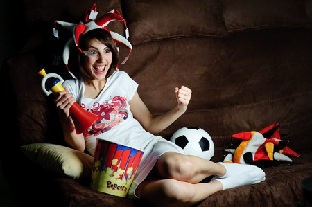 An image of a girl on a sofa watching football on TV photo