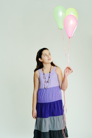 An image of a young girl with three balloons photo