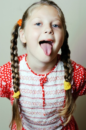 An image of a little girl showing her tongue photo