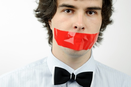 An image of a man with a tape on his mouth photo