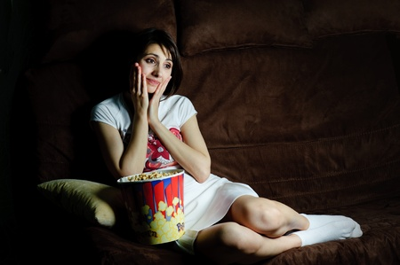 An image of a girl on a sofa watching TV Stock Photo