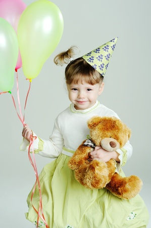 A portrait of a little girl with a teddy-bear and balloons photo