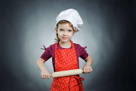 rollingpin: An image of a nice girl in a white hat with a rolling-pin Stock Photo