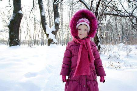 ropa de invierno: Una imagen de una niña en un parque en invierno Foto de archivo