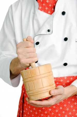 An image of a wooden mortar in chefs hands photo