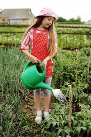 watering can: Girl watering plants in a kitchen-garden