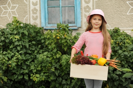 An image of a girl with a wooden box of vegetables photo
