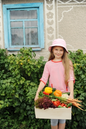 An image of a girl with a box of vegetables photo