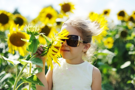 A little girl in sunglasses with sunflower photo
