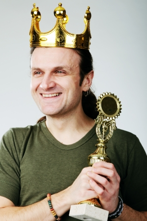 A man with a toy plastic crown on his head and with prize photo