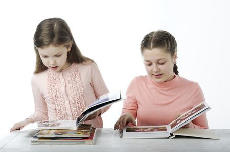 barrettes: Little girls read books at the table isolated on white