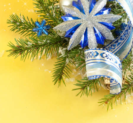 Christmas ornaments and tree branches on a yellow background photo