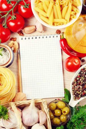 libro de recetas en blanco sobre una mesa con verduras Foto de archivo