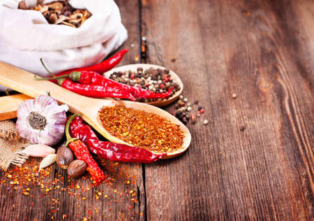 Pepper and spices on wooden background photo