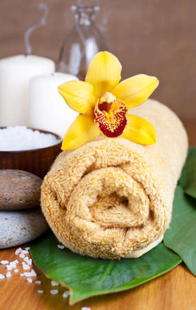 day spa: Orchid flower and towel, zen stones, salt,   over wooden surface