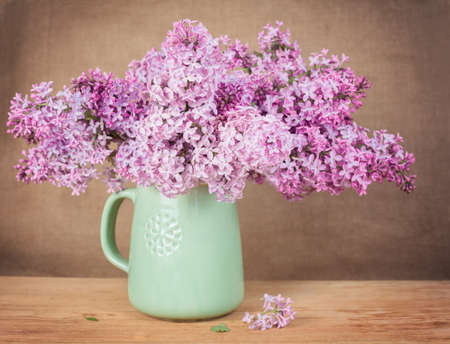 Lilacs in a green jug on a wooden surface photo