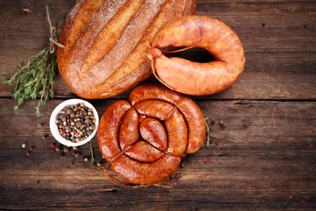 cold cuts: Sausage, bread and spices on wooden surface Stock Photo