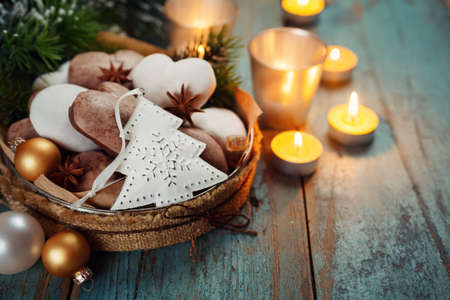 Christmas decoration, gingerbread, candles, fir on a wooden board