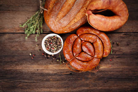 Sausage, bread and spices on a wooden table photo