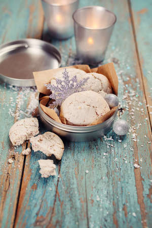 blue toned: Christmas decoration, cookies, candles, on a wooden table.