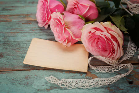 Pink roses on a wooden table. Vintage photo