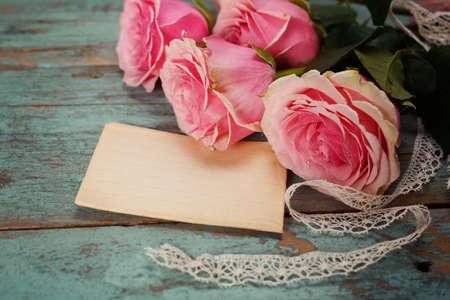 Rosas rosadas en una mesa de madera. Vendimia