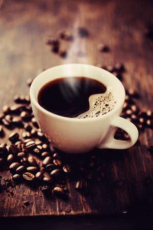 bönor: Ångande kopp nybryggt kaffe. Grunt skärpedjup